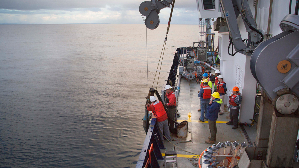 An image of people deploying a discharge hose and studied sediment plumes from the deep sea
